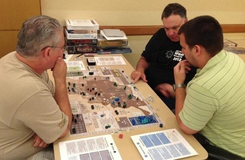 Mike points at a Resource marker in a prototype of A Distant Plain while Gene Billingsley and Jordan Kehrer look on.